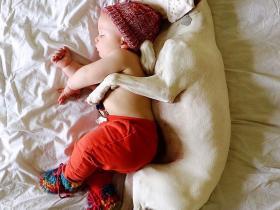 可爱的宝宝与狗狗一起睡觉,照片背后有一个暖心的故事